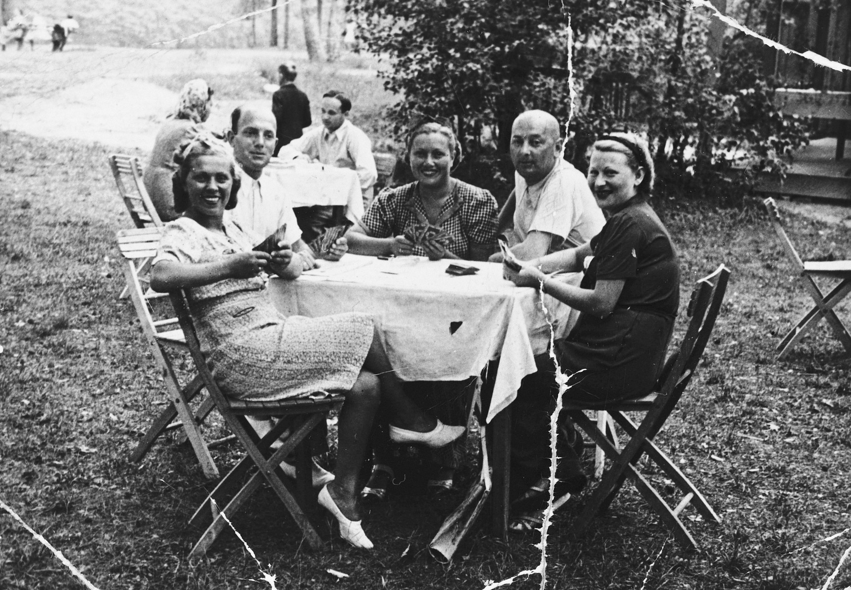 A group of friends play cards outside.  Pictured on the left are Rudolf and Dora Friedmann.