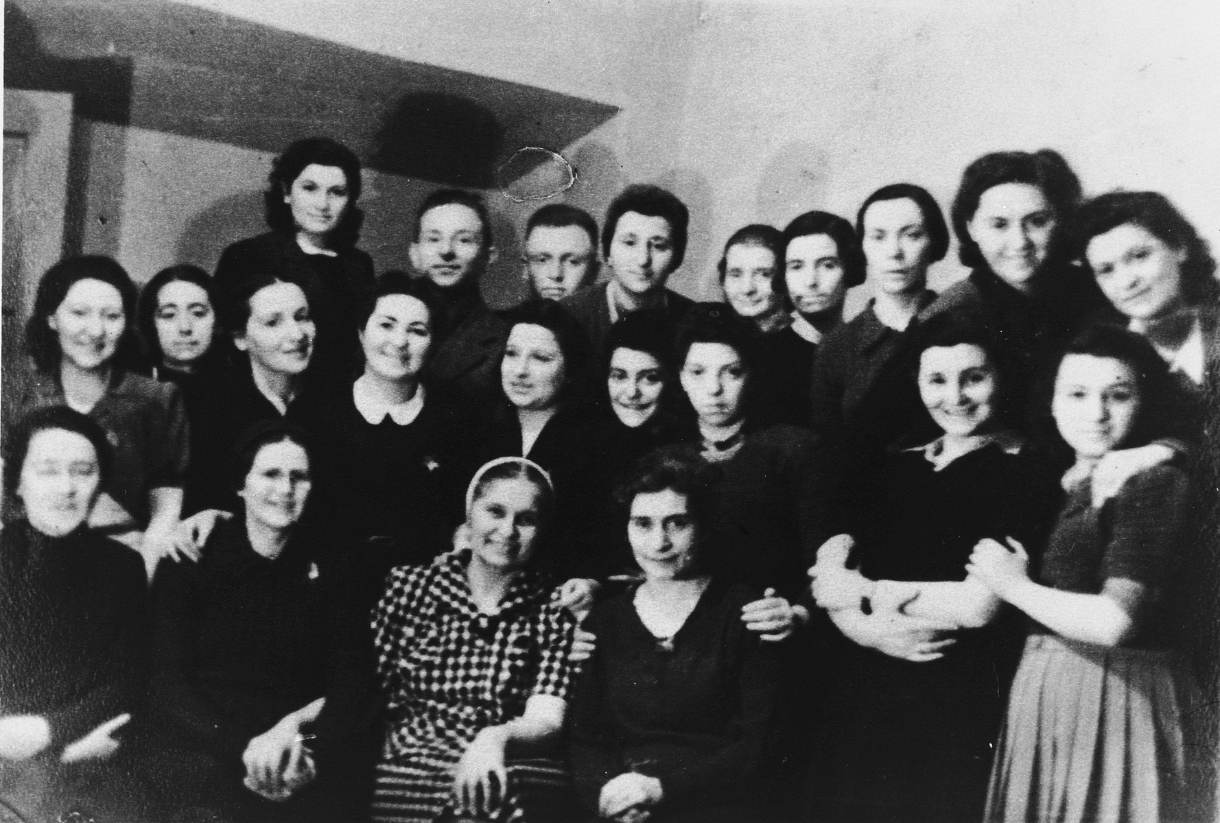 Group portrait of the staff of the coffee house in the Vilna ghetto.  Among those pictured are: Liza Beigel (top row, right), her sister, Mariussa Kowarsky (front row, standing, second from the right), Shura Kessler (middle row, left) and the head of the cafe, Mrs. Cyrynska (front row, center, in the checked dress).