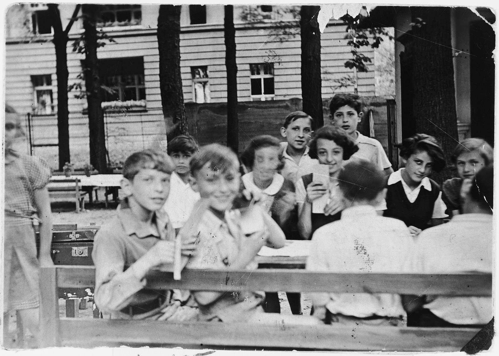 Children sit around a picnic table in a Jewish summer camp in Berlin  Felix Zajac is standing at the back.