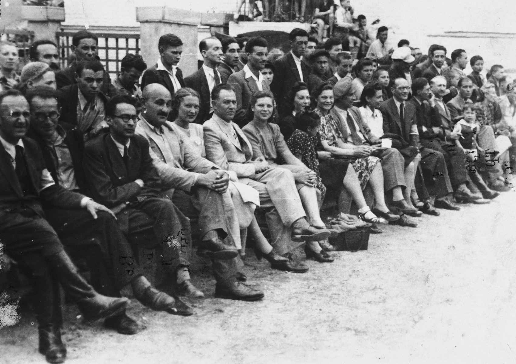Jewish officials of the Vilna ghetto are seated in the audience at a sporting event.  Among those pictured are Ferdinand Beigel (front row, left), Salek Desler (chief of police, fourth from left) and his wife, Jacob Gens (front row, sixth from the left).  Next to him is his daughter Ada, and his wife (tenth from left).