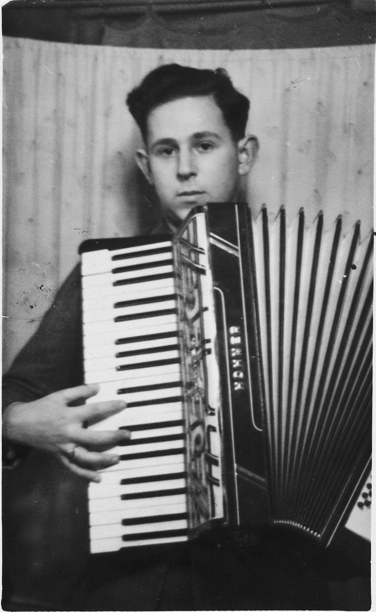 Portrait of Wilhelm Beigel playing an accordian in a displaced persons camp in Gailingen, Germany.