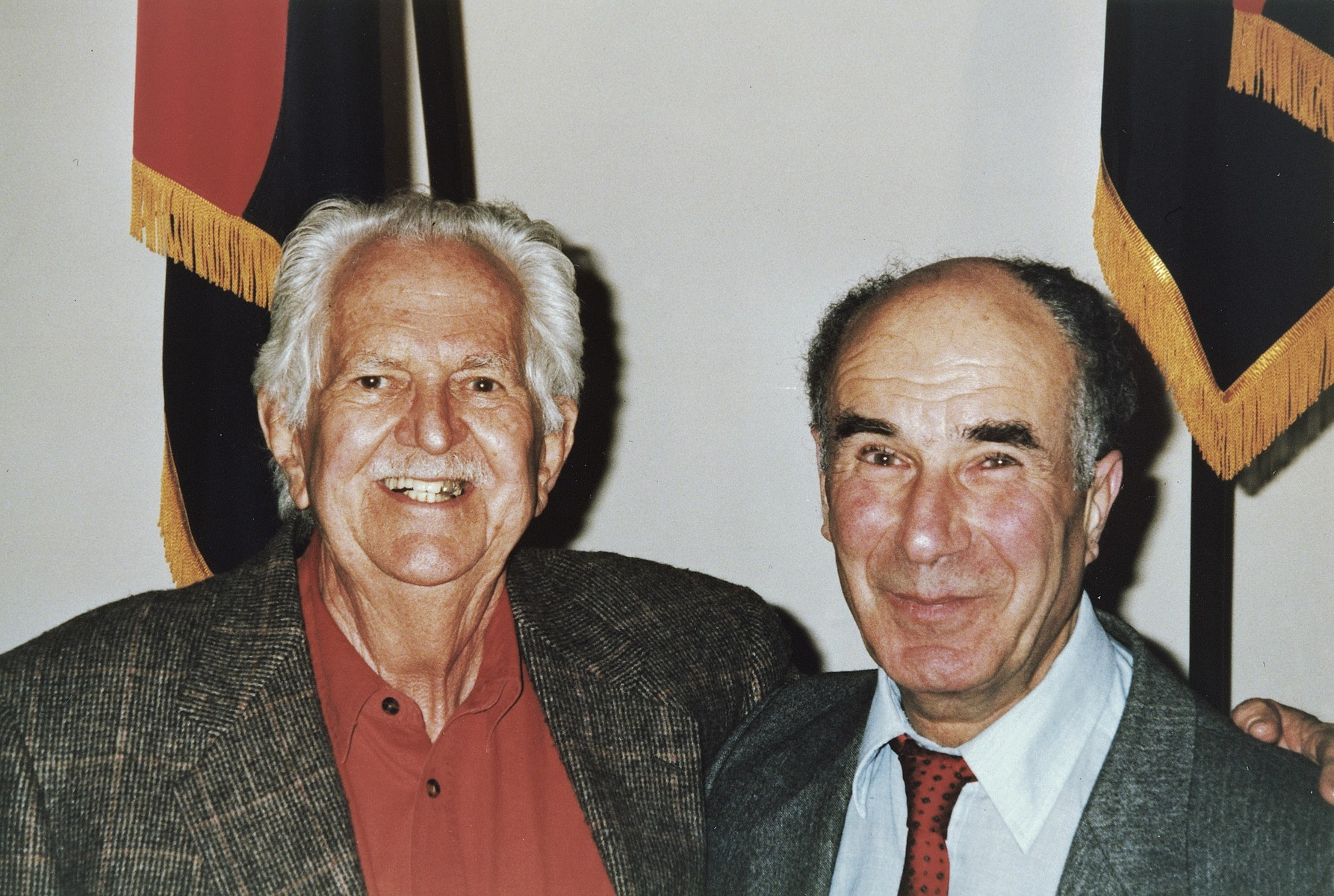 Portrait of American liberator Arnold E. Samuelson (left) and survivor George Havas (right) in front of the liberator flags at the U.S. Holocaust Memorial museum.