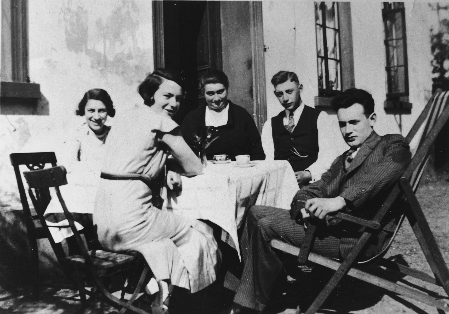 A German-Jewish family enjoys a cup of coffee in a courtyard in Aurich.  Pictured from left to right are Herta Goldschmidt, Emmi Samson, Mrs. Samson, Josef Samson and Herman Knurr.  Herta Goldschmidt left Germany for America in March 1939.  All of the Samson family perished.