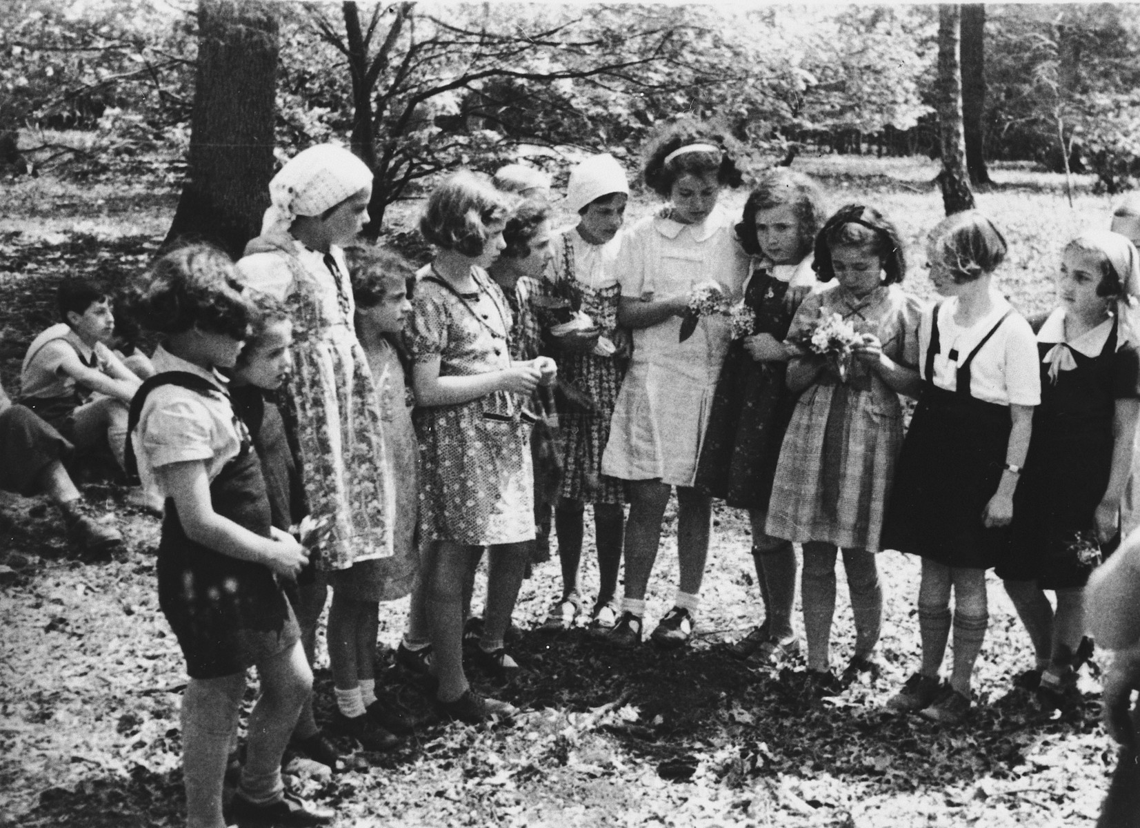 A group of girls stand in a line holding flowers in the Chateau de La Guette children's home.  Among those pictured are Ellen Schwerin (second from right), Helli Buchholz (third from right), Rita Buchholz (fourth from right) and Berty Heiberg (fifth from right).