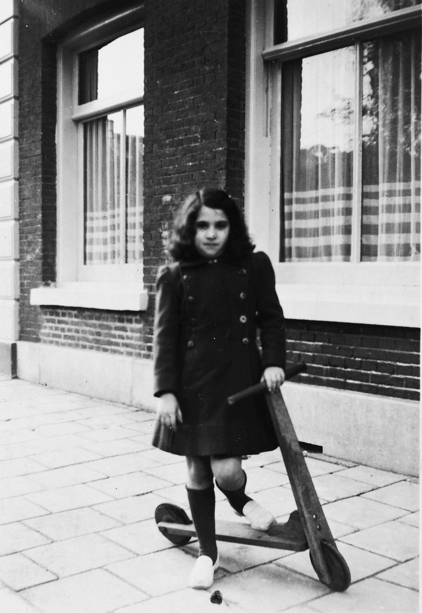 Ruth Franken poses next to her scooter on a sidewalk in Amsterdam.