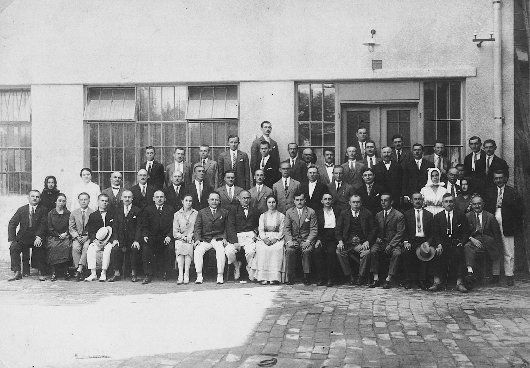 Lajos and Ferenc Fenyves pose with the staff of their printing plant.  Lajos and Ferenc Fenyves are seated in the center wearing white pants.