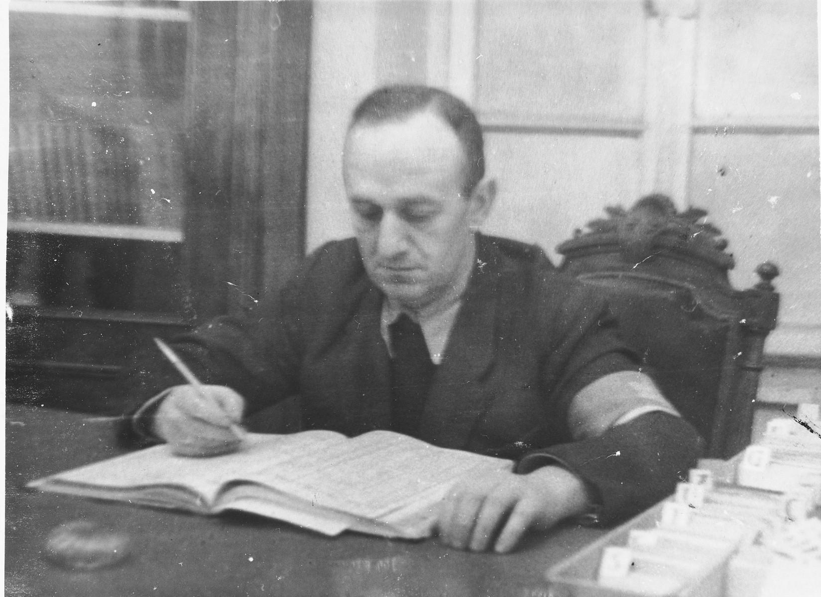 Ghetto police chief Ferdinand Beigel writes in a ledger at his desk in the Vilna ghetto.
