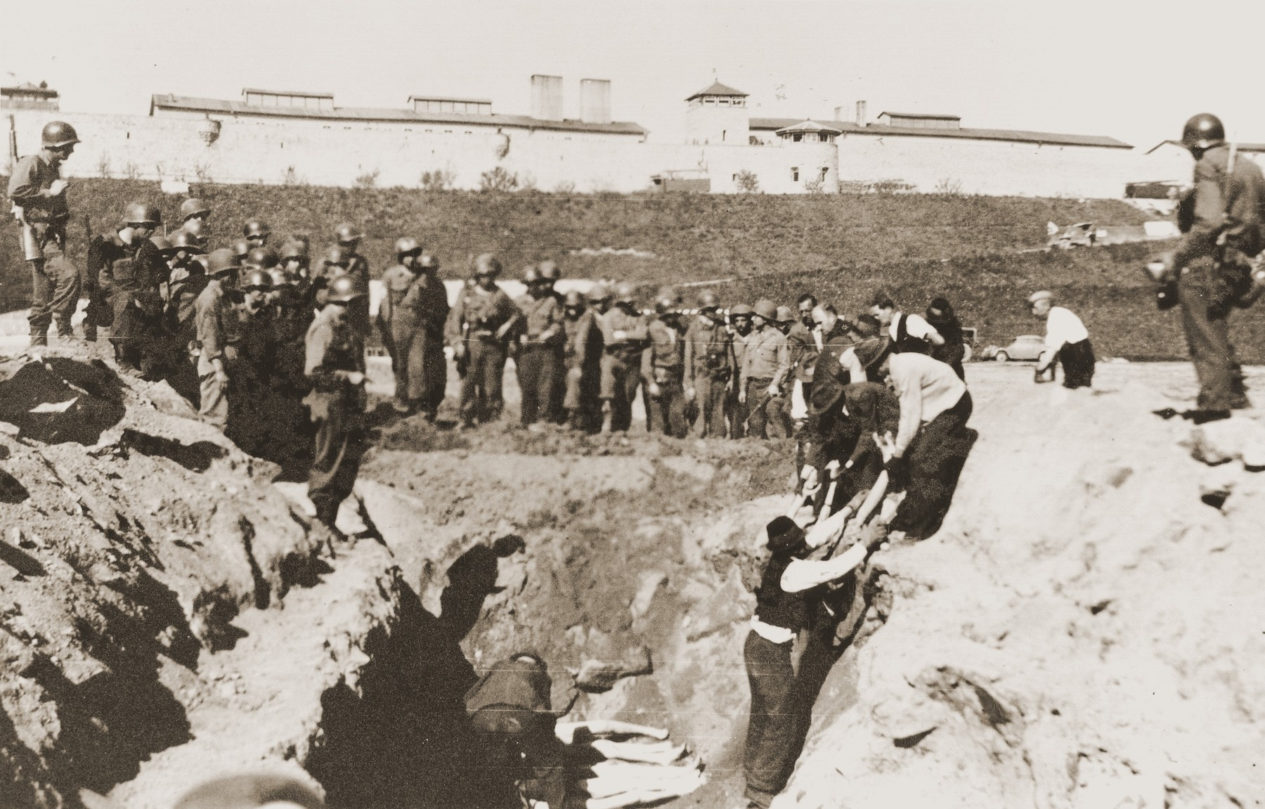 American soldiers watch as Austrian civilians lay the bodies of Mauthausen victims in a mass grave dug in the former SS soccer field.  Ray Buch stands at the right holding a camera.  Officers Chas Thurston of Pennsylvania and Harry Brown of Texas are among the American soldiers standing guard.