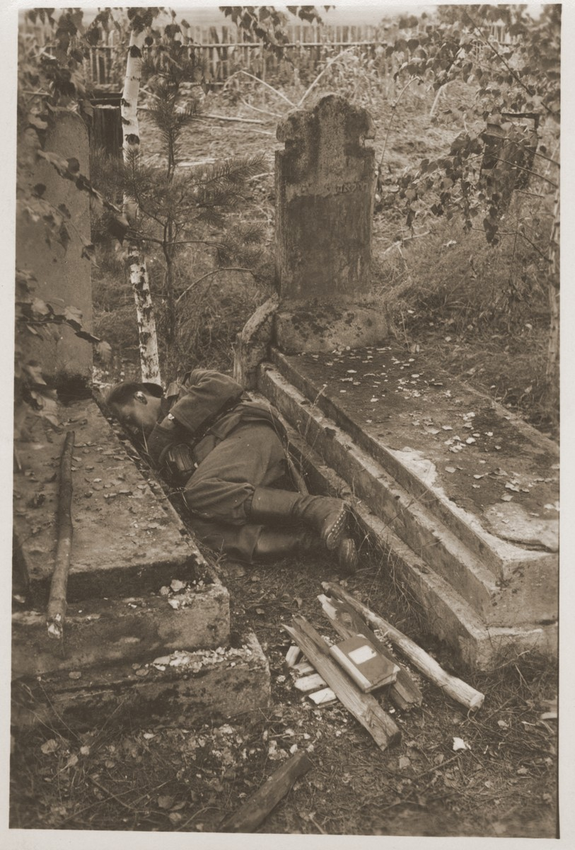 A German soldier sheltered by two tombs gets some sleep in a Jewish cemetery.