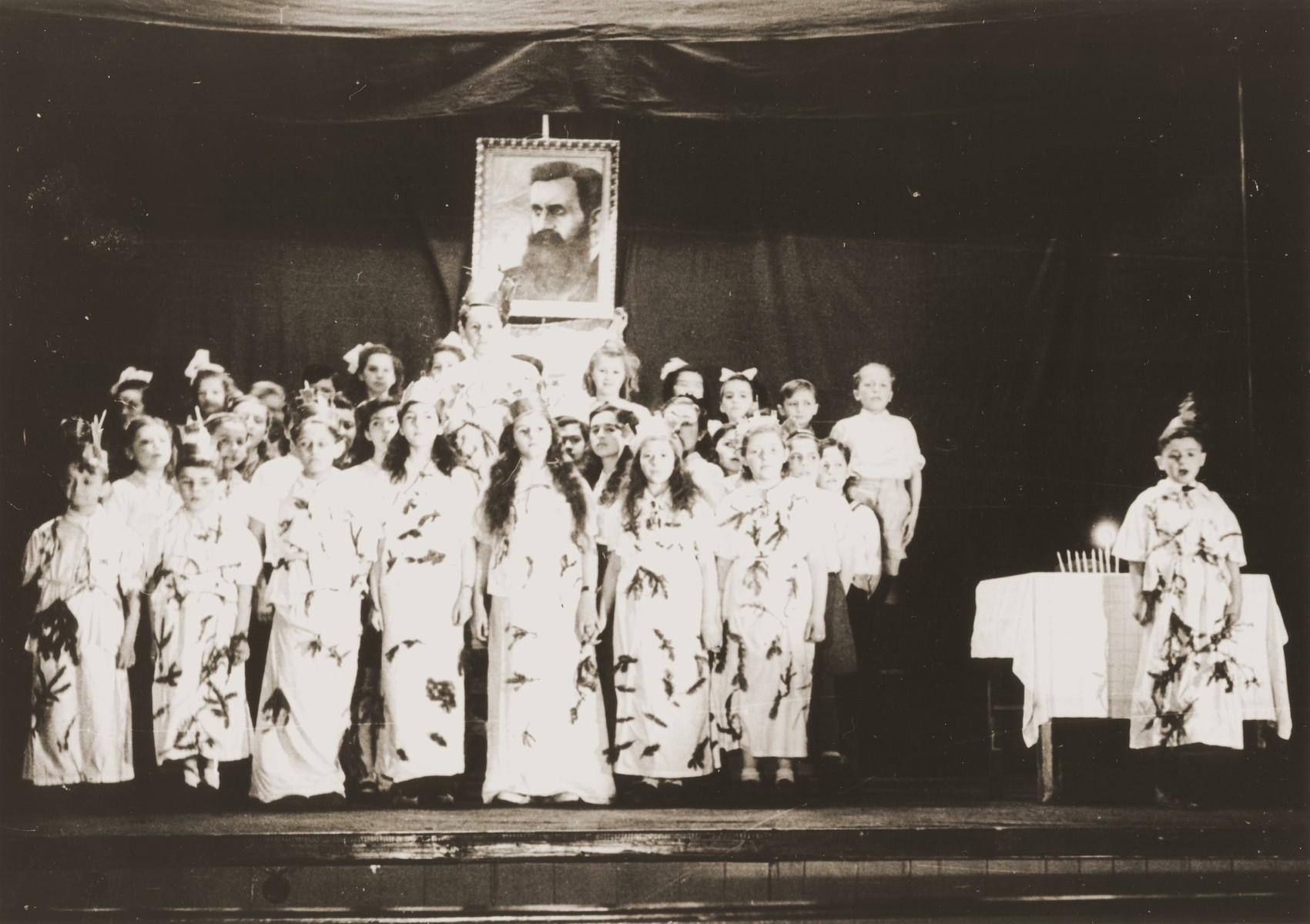 Children put on a Hannuka play in front of a portrait of Theodore Herzl in the Feldafing DP camp.