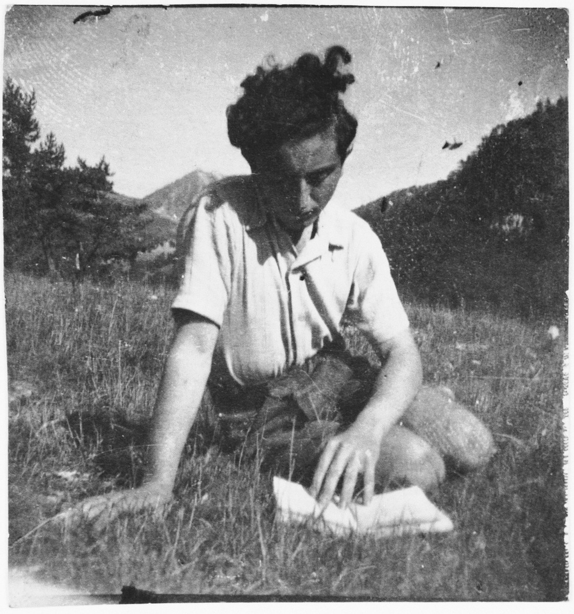 Jewish refugee Eryk Goldfarb reads a book on a grassy hillside while living in hiding in Col de Menee, France.