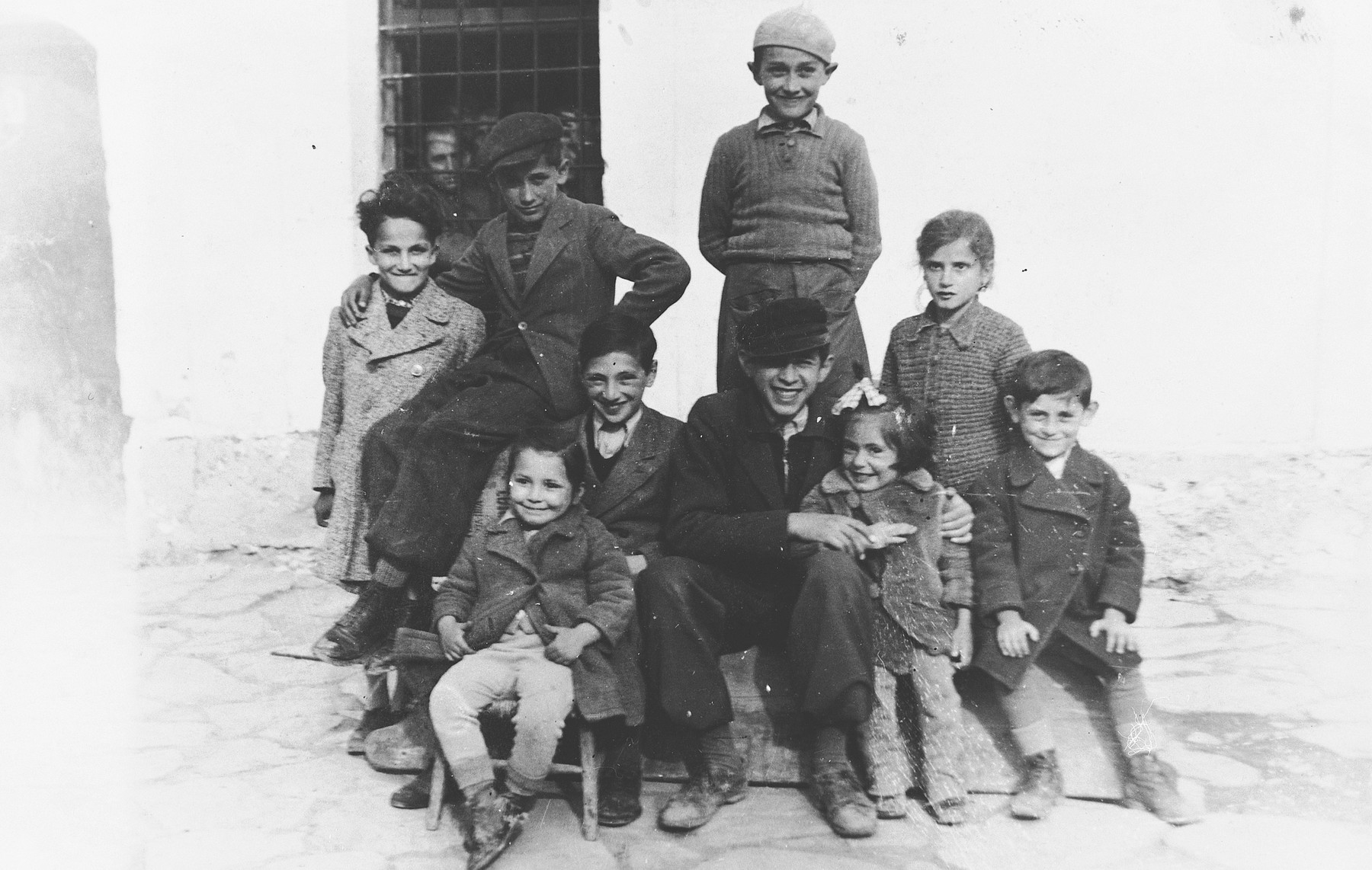 Group portrait of the children of Jewish refugee families incarcerated in the Pristina prison.    Pictured clockwise from the upper left are: Jasa Altarac, Nidja Konforti, Michael Konforti, unknown, Gavra Mandil, unknown, Ralle Jakovljevic, Marki Azriel, and Irena Mandil.