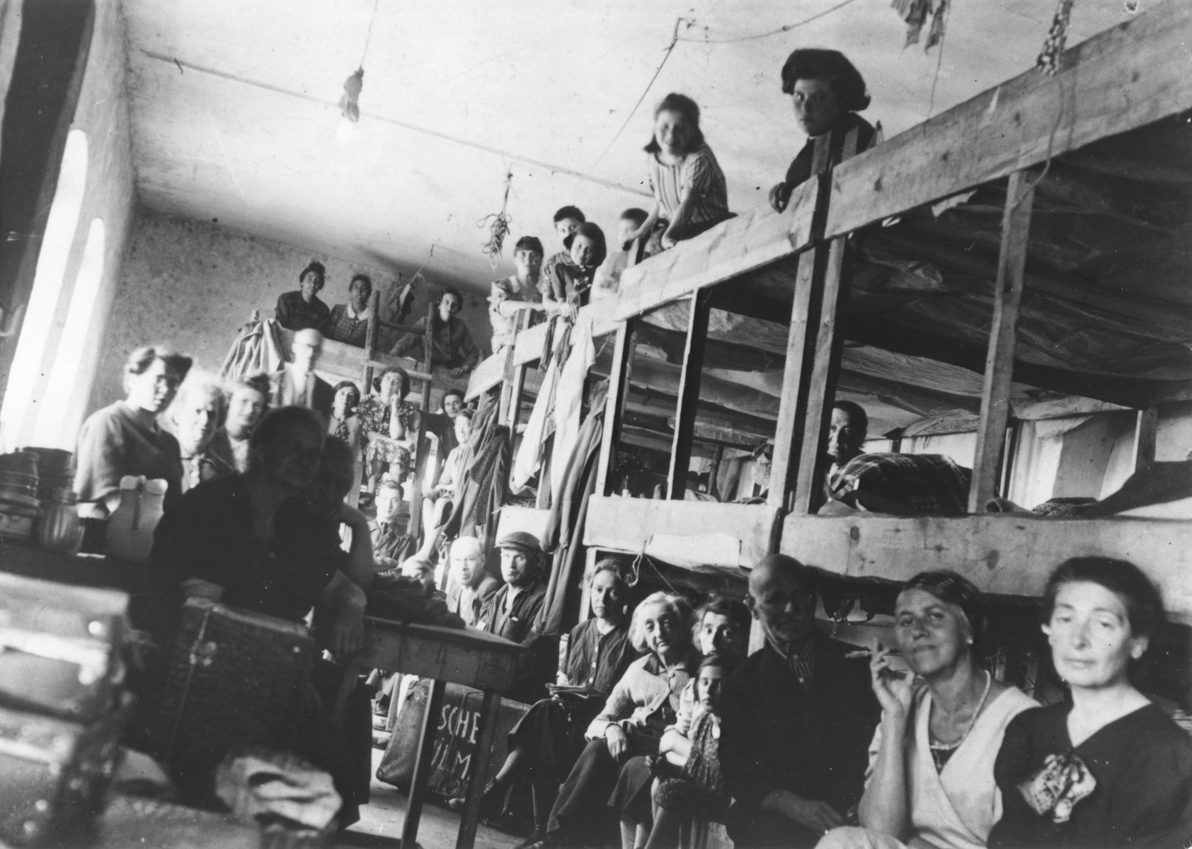 Jewish women from Vienna sit on three-tiered wooden bunks in a barracks in the Opole Lubelskie ghetto.