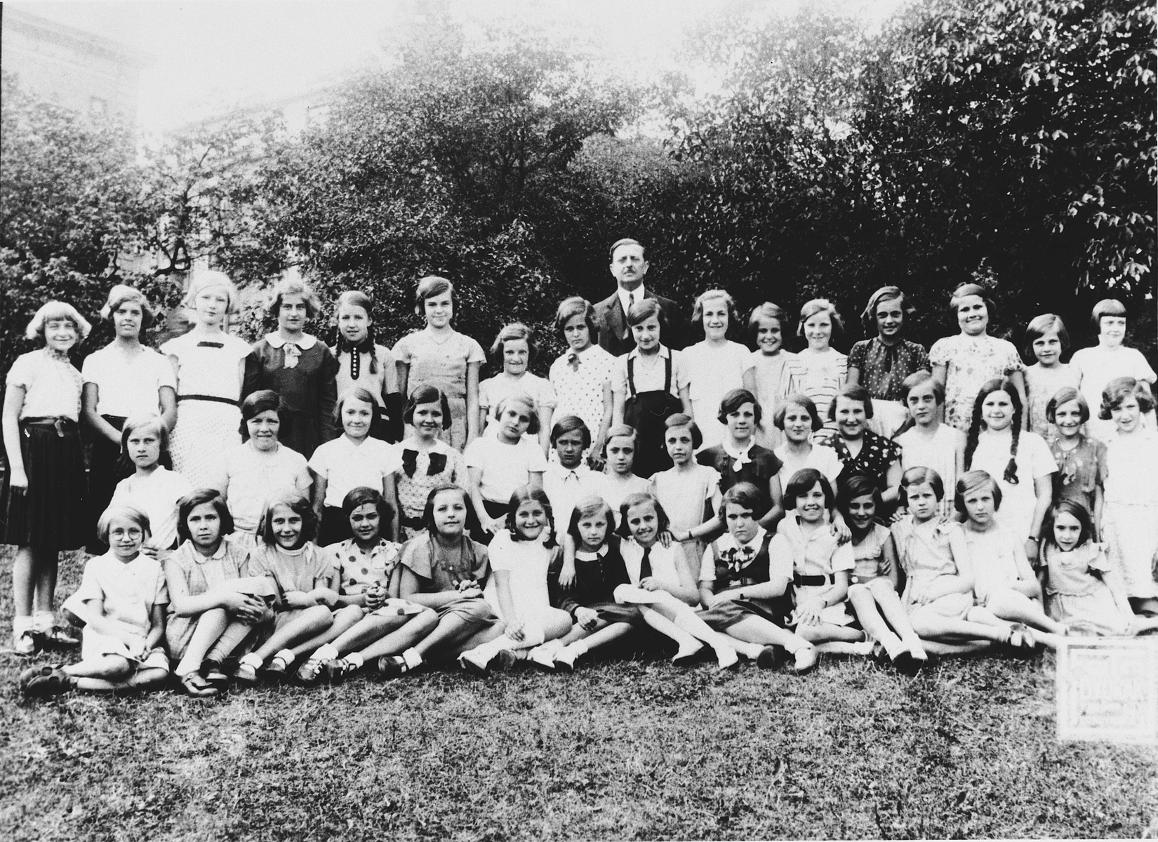 Group portrait of children from a public grammer school in Prague on an outing.  Some of the girls are Jewish.  Among those pictured is Hana Fuchs.
