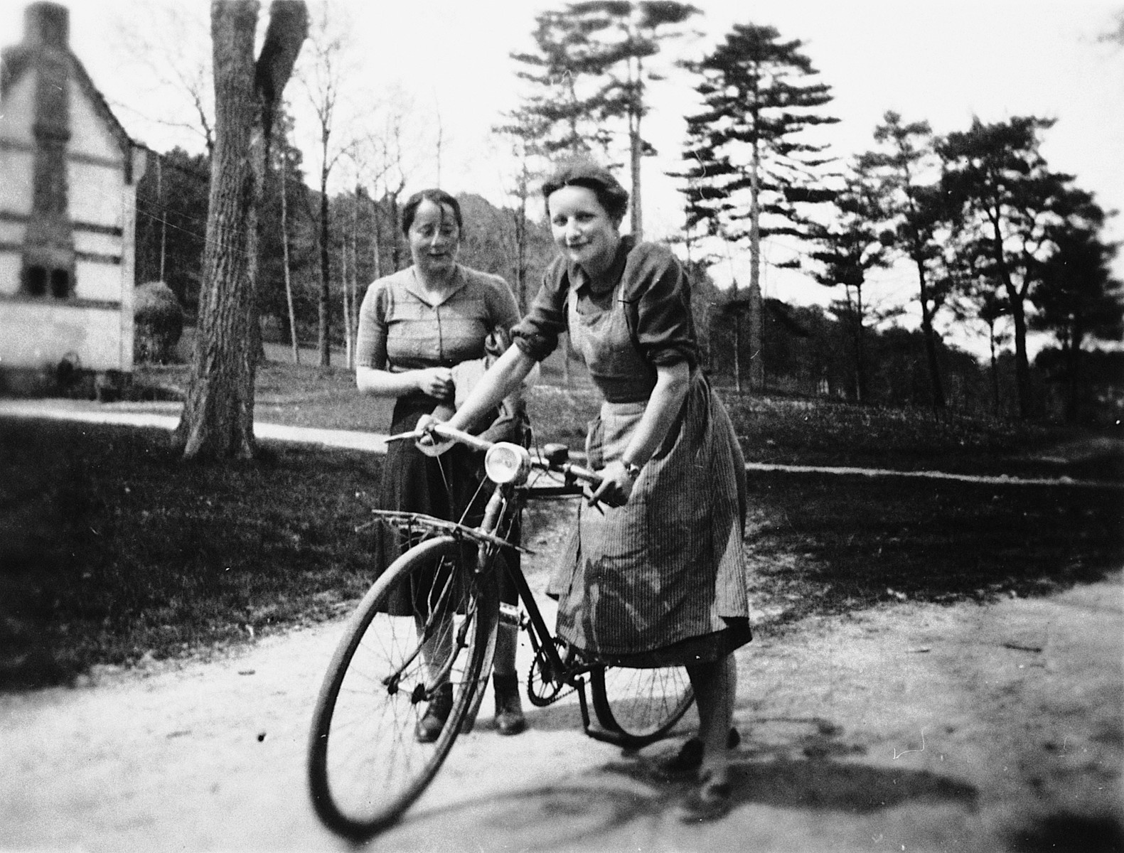 Magrit Taennler rides a bicycle near Chateau de la Hille while Ms. Tobler looks on.