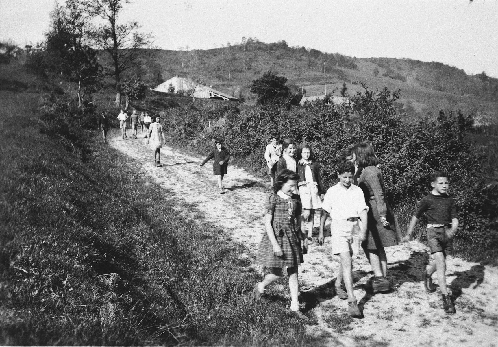 Children go for a walk in the countryside near Chateau de la Hille.  In foreground center, with white shirt and dark hair, Paul Schlesinger. The girl behind his right shoulder, in dark sweater and light dress (wearing glasses) is Gonda Weinberg (now Connie van Praag).