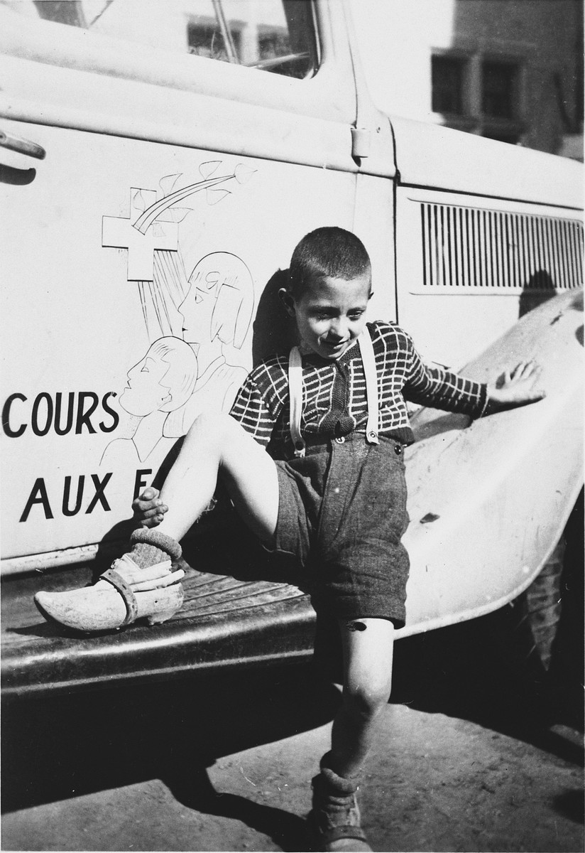 Guy Perry leans against a van belonging to the Secours Suisse outside the Chateau de la Hille.