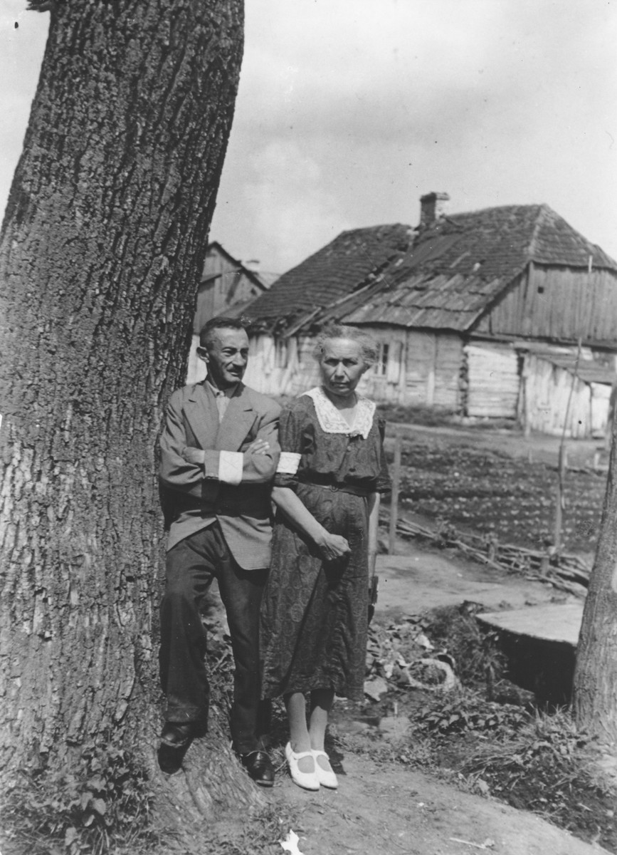 "Wilhelm and Johanna Schischa pose next to a tree wearing armbands in the Opole Lubelskie ghetto.  The original photo is inscribed to their children, ""For our Lilli and Edi."""
