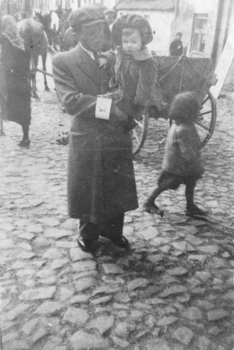 Majer Sztajman poses on a cobblestone street in the Opatow ghetto holding his baby daughter, Mania.