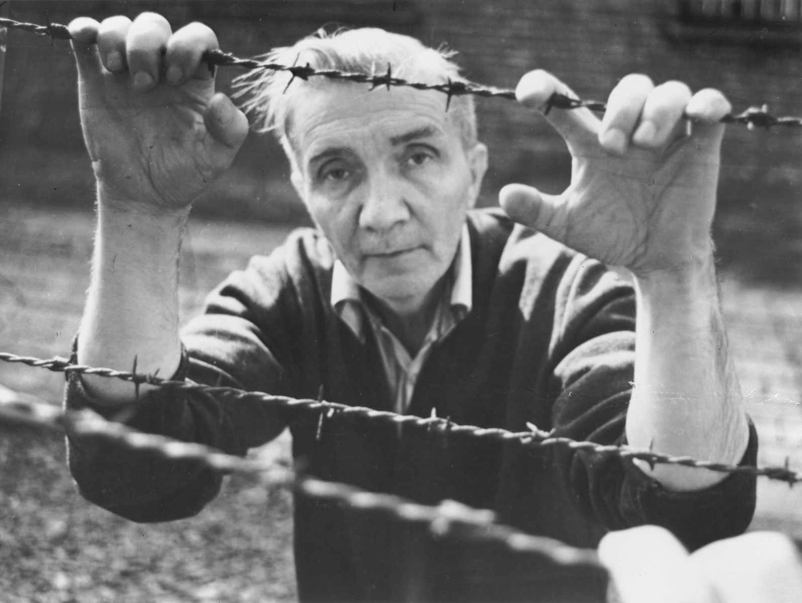 Aleksander Kulisiewicz poses holding on to the barbed wire fence at a former concentration camp [possibly Sachsenhausen] during a performance of his collected concentration camp music.