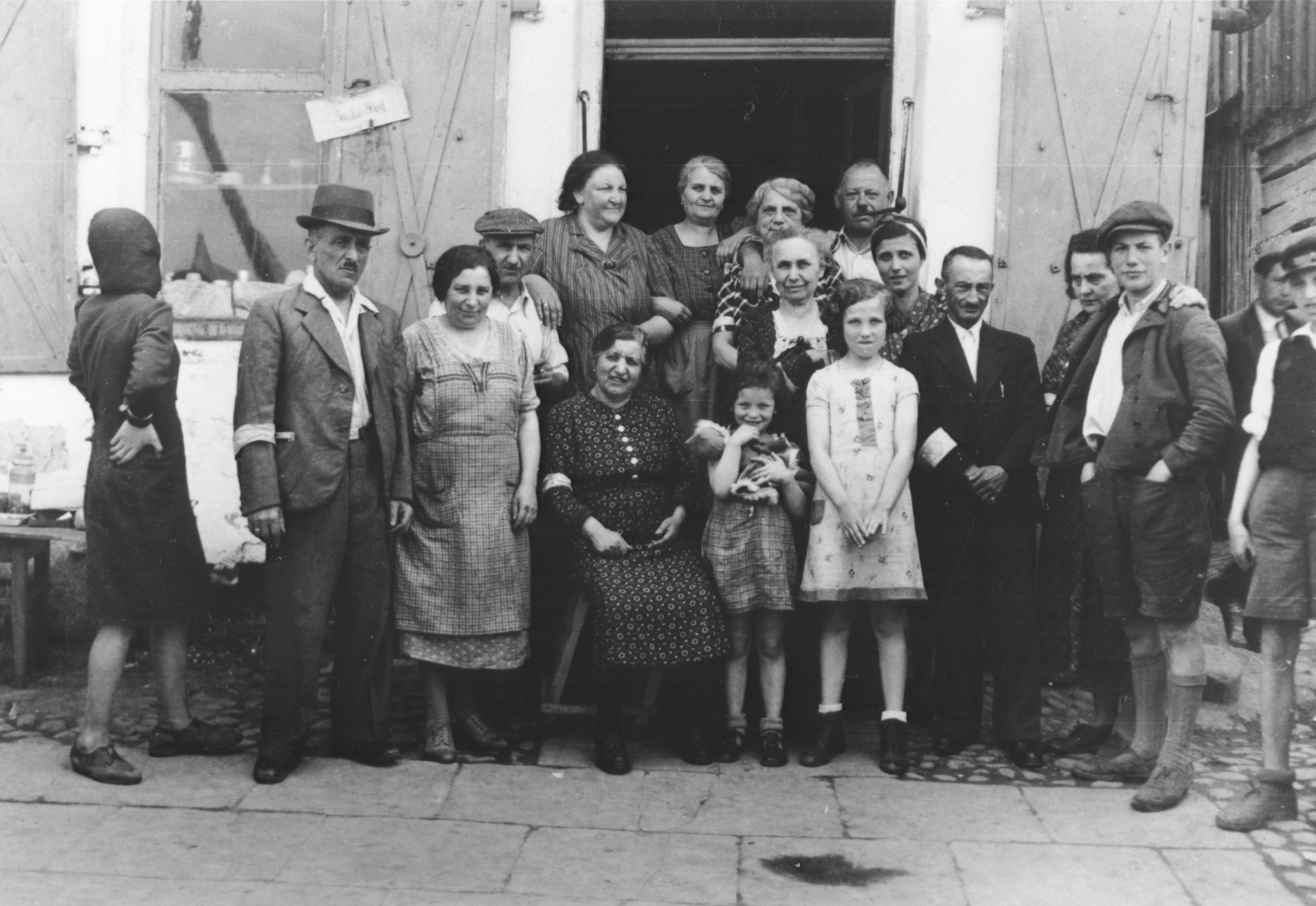 Group portrait of Jewish men, women and children on a street in the Opole Lubelskie ghetto.  Among those pictured is Wilhelm Schischa (front row wearing an armband, beside the girl in the light dress) and Johanna Schischa (center, behind the two girls in the front row).