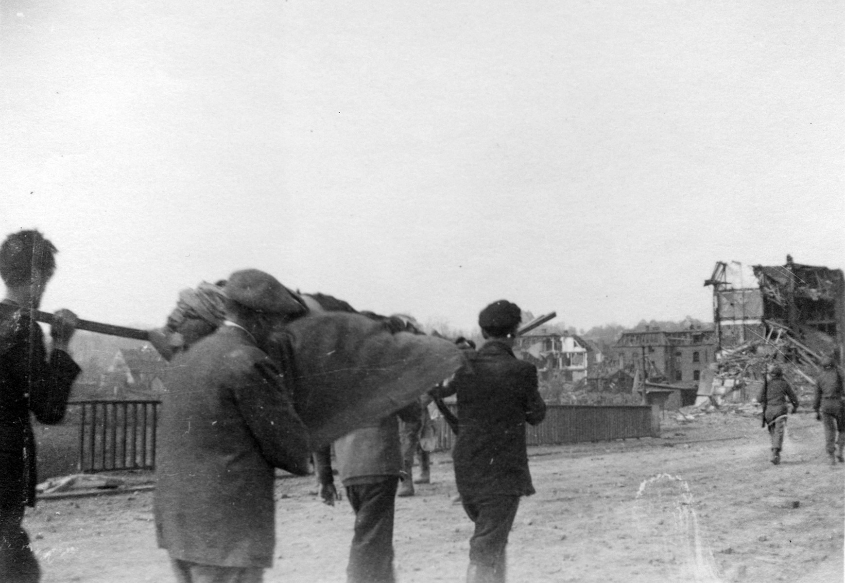 Four German civilians bear a stretcher holding the body of a Nordhausen concentration camp victim who is being removed from the camp to a nearby site for burial.
