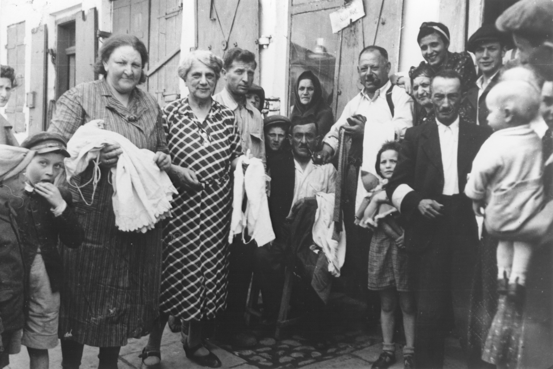 Group portrait of Jewish men, women and children on a street in the Opole Lubelskie ghetto.  Among those pictured is Wilhelm Schischa (second from the right wearing an armband).
