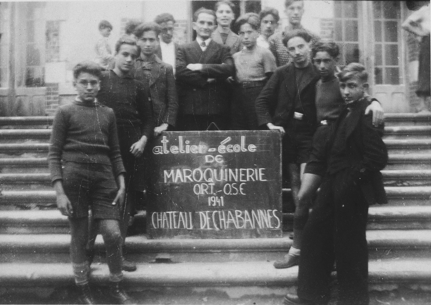 Students in a leatherworking class pose outside on the steps of the Chabannes children's home.   The instructor, Mr. Kenig, is pictured in the center, behind the sign.