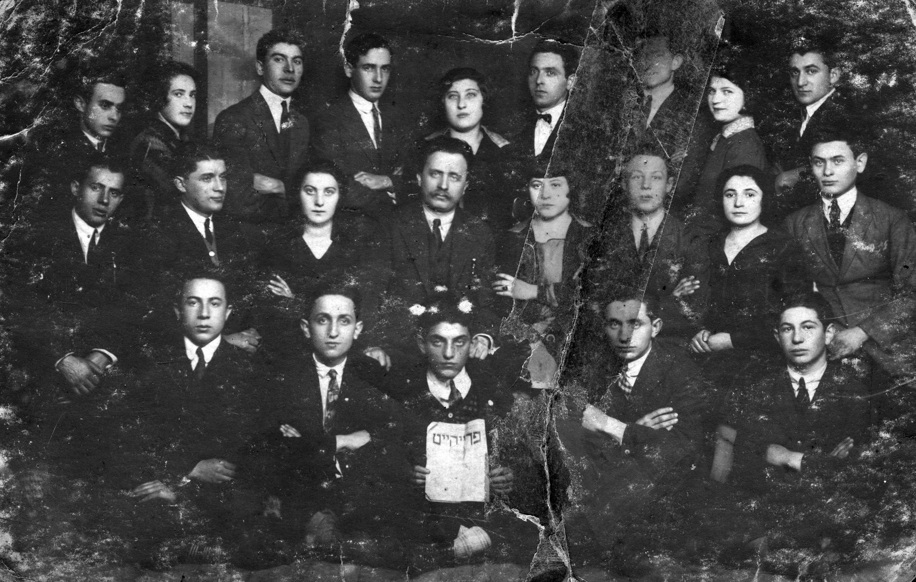 Group portrait of members of Poalei Zion Zionist youth organization in Bedzin.  The young man in the front row holds an issue of a Zionist newspaper 'Freiheit' [Freedom].  Among those pictured is Berl Loker, the leader of the group (second row, center) and Anszel Borzykowski (second row, third from the right).