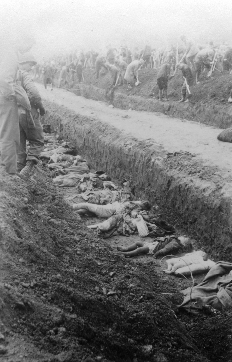 The bodies of prisoners killed in the Nordhausen concentration camp lie in an open mass grave.    In the background, German civilians fill in another mass grave under the supervision of American troops.