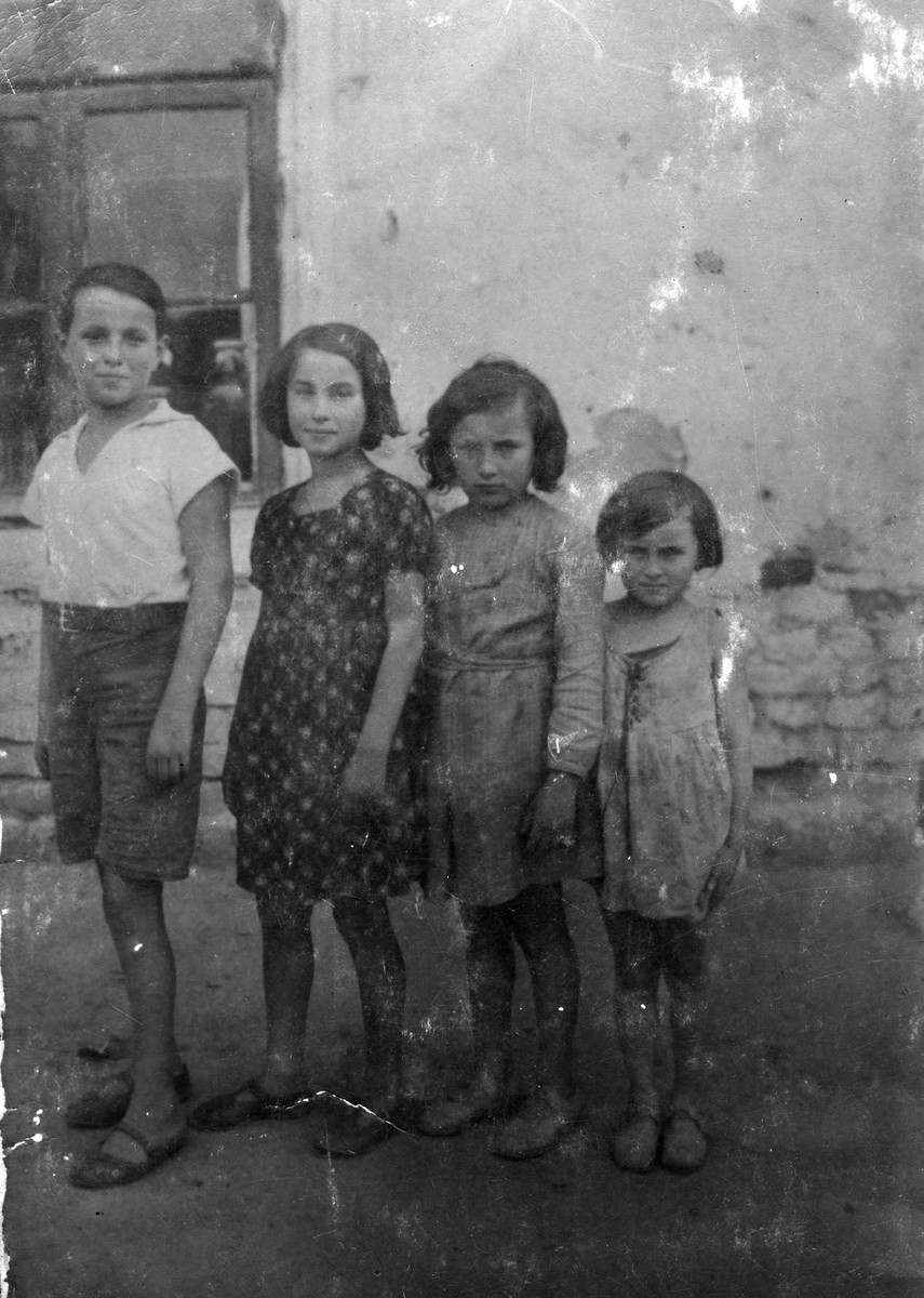 Four Jewish siblings pose outside their home in Sosnowiec, Poland.  Pictured from left to right are: Tzvi, Genia, Frania and Sala Dunski.