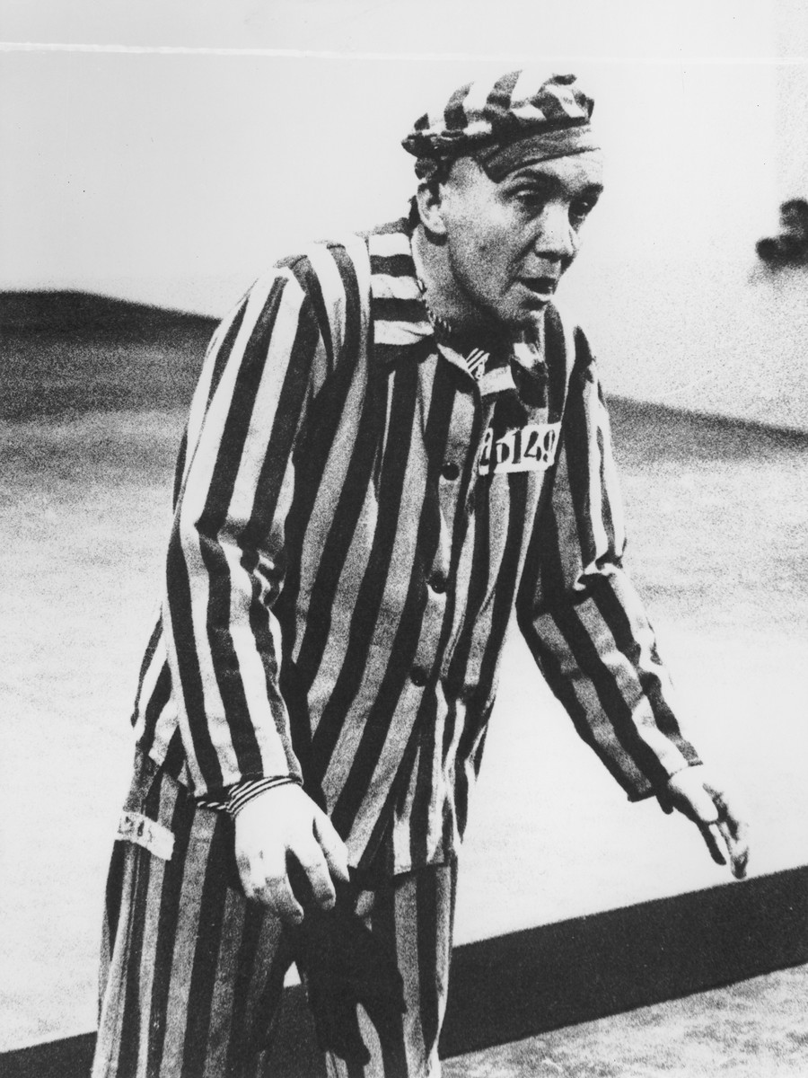 """Aleksander Kulisiewicz, dressed in a concentration camp uniform, performs the """"Choral, from the Depths of Hell"""" at the Theater Communale in Bologna, Italy."""