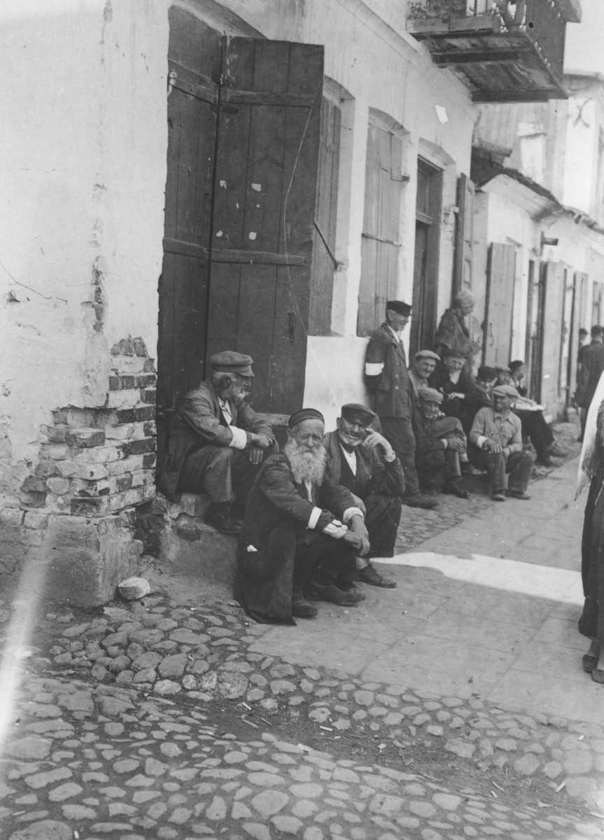 "Jewish men wearing armbands sit outside a row of buildings in the Opole Lubelskie ghetto.  The original caption reads: ""Just sitting around the whole day from morning til midnight with nothing to do."""