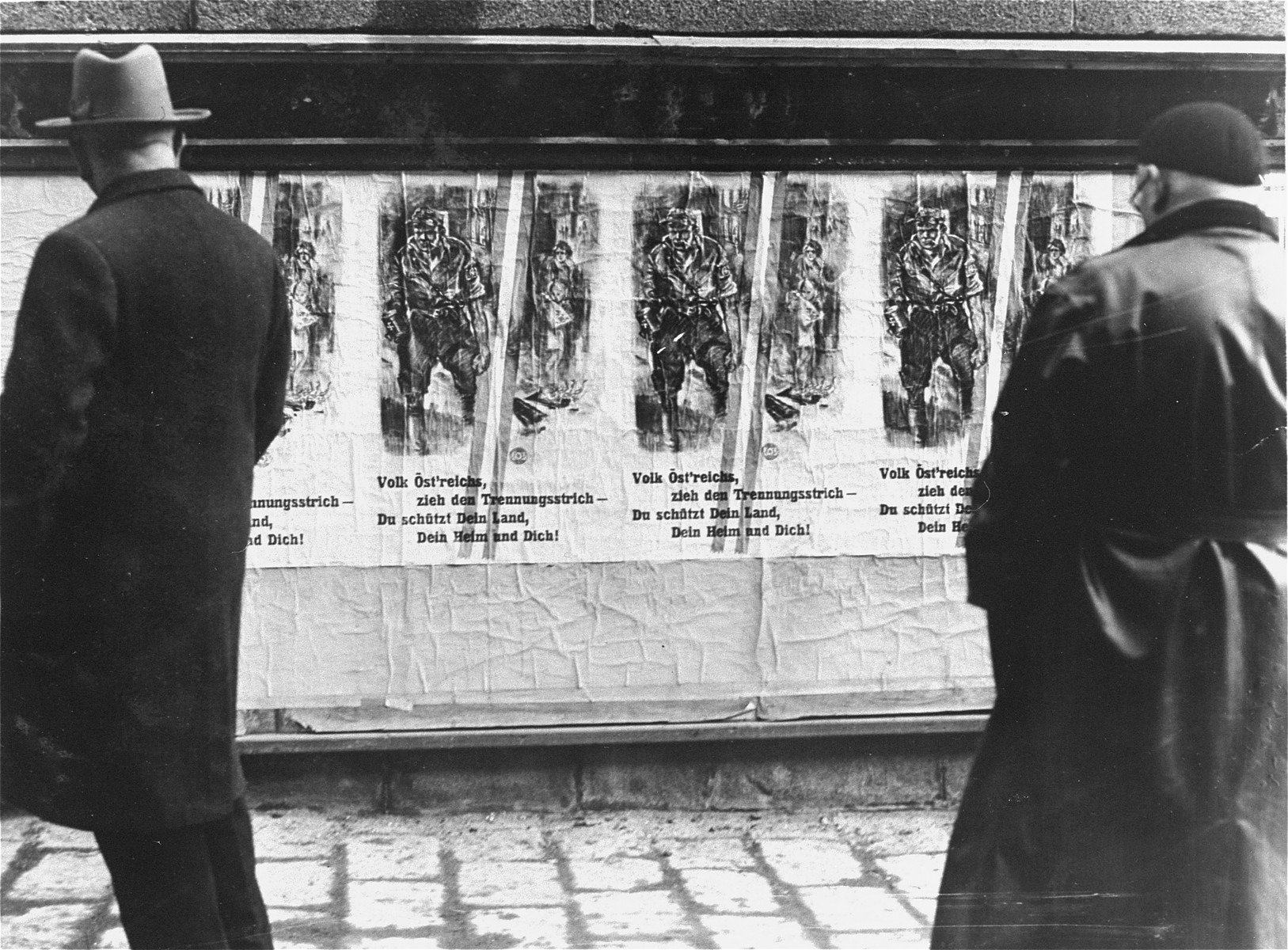 Viennese pedestrians read an anti-Nazi poster posted by the Ministry of Propaganda on a billboard in the streets of the city.