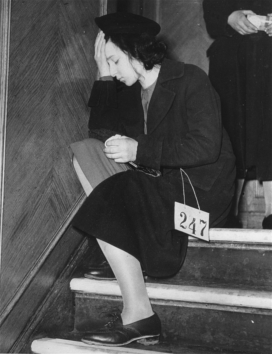 A Jewish youth, wearing a numbered tag, sits on a staircase with her head in her hands after her arrival in England with the second Kindertransport.