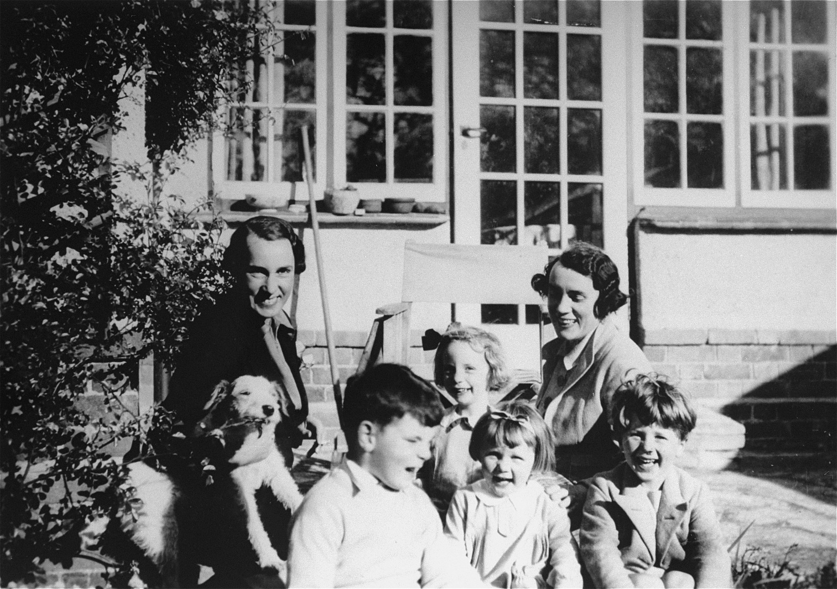 Two British Quaker women who served as foster parents to Jewish Kindertransport children, pose with a group of young children in Bristol.  Mary Moar is pictured on left; her sister Mrs. Baker, on the right.