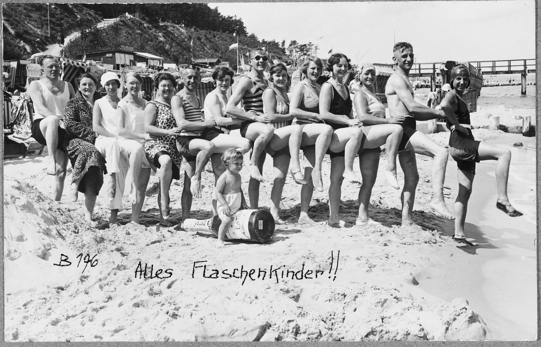 "Friends and relatives of the Glueckstein family pose in their bathing suits on a beach in Germany, while the toddler, Fritz Glueckstein, sits in front on an inflatable ""wine bottle""."