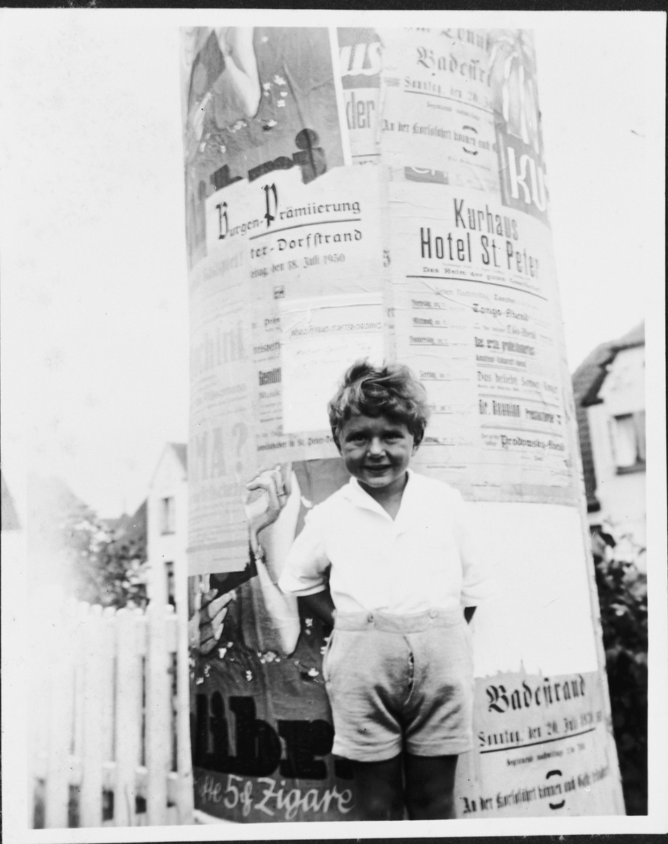 Fritz Glueckstein poses in front of a kiosk covered with announcements and advertisements.