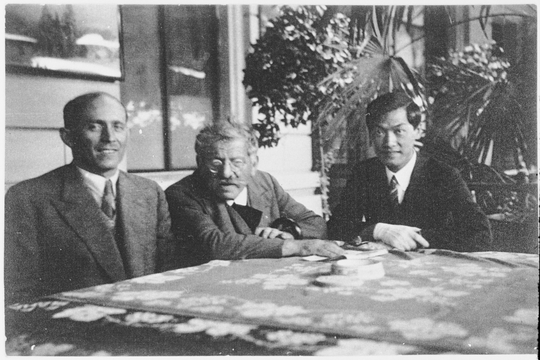 Sexologist and sex reformer Magnus Hirschfeld (center) with his co-worker Bernhard Schapiro (1885-1966) and his Chinese (in exile) friend and pupil Tao Lee, sitting at a garden table, unknown place and date.  (Archiv für Sexualwissenschaft, E. Haeberle, Berlin)