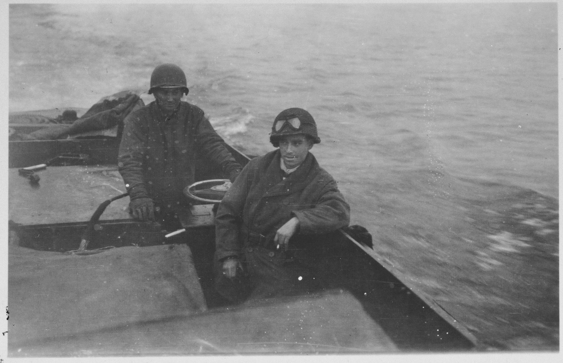 Two American soldiers cross the Rhine River into Germany.  Pictured in the foreground is Jack Caminer.