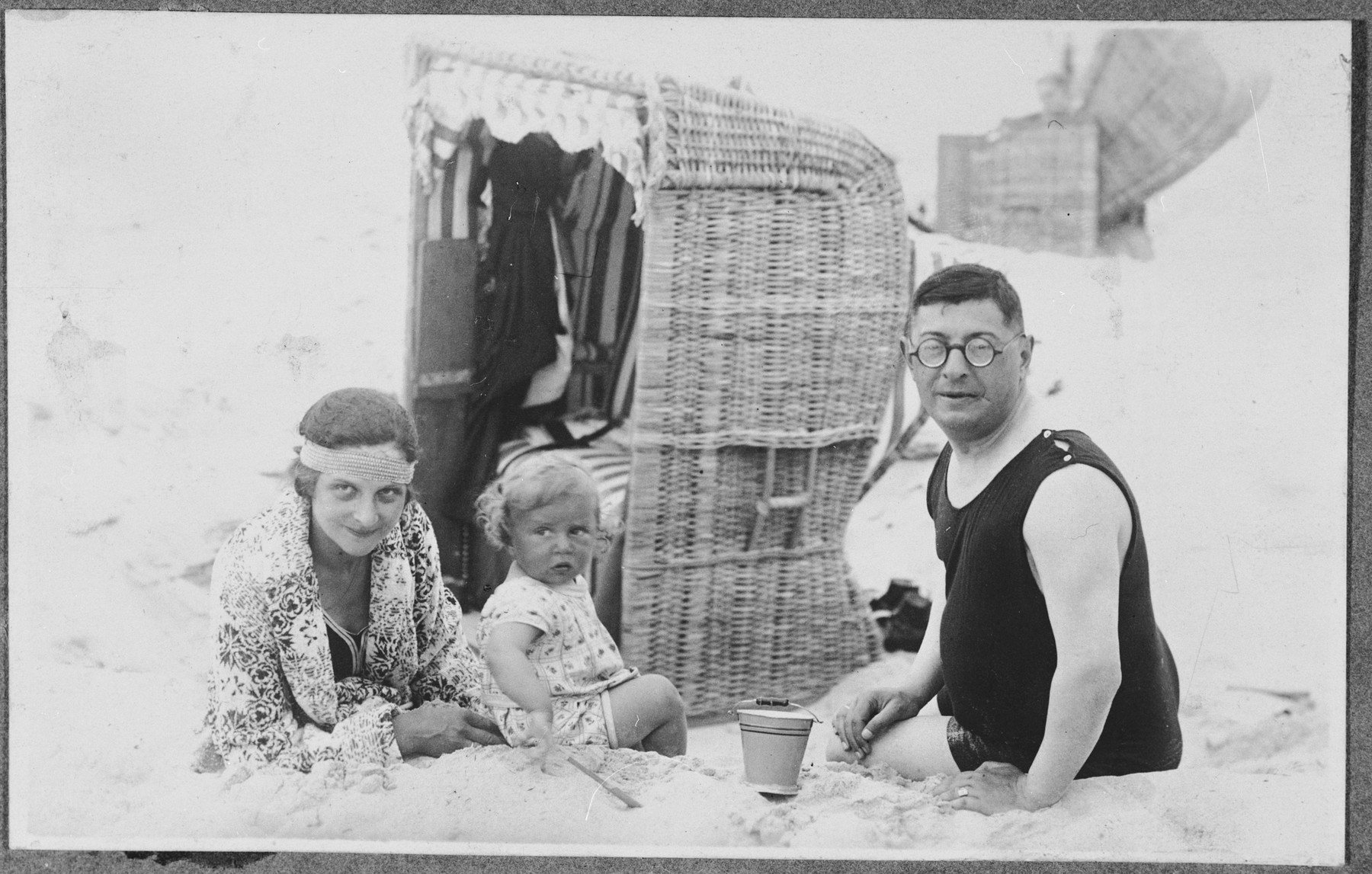 The Glueckstein family relaxes on a beach in front of a cabana.  Pictured from left to right are Hedwig, Fritz and Georg Glueckstein.