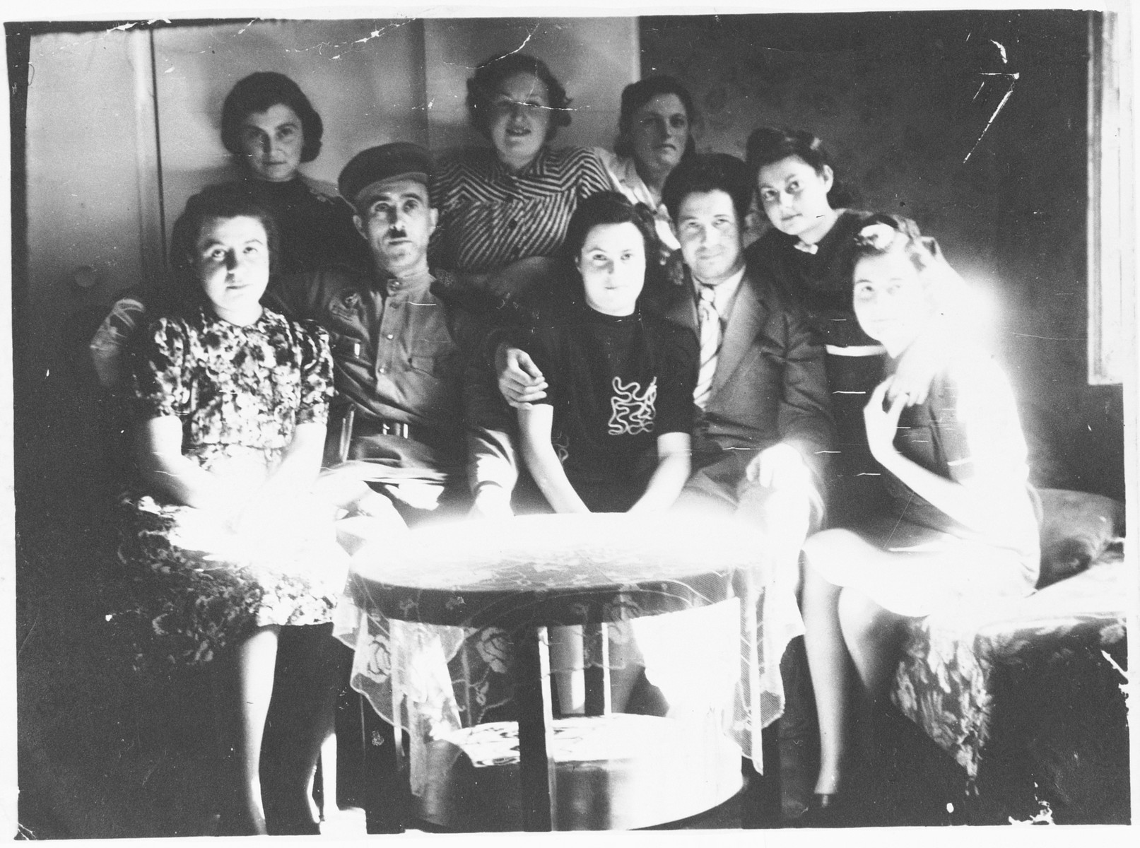 A group of Jewish DPs gather around a table in Koeslin, Poland.  Pictured seated in the front row, from left to right, are:  Esther Poupko, unknown, Susanne Strauss, her fiance Herman Taube, Gerda Lehman and Vera Sklan.  Standing behind in the center is Hannelore Marx.