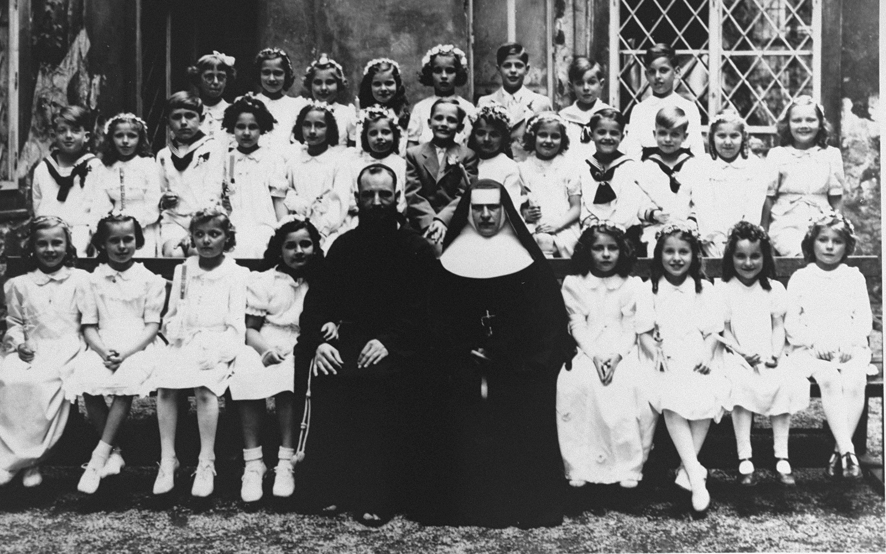 Group portrait of teachers and students in a first communion class at the Ursulinen convent school in Vienna.    Among those pictured is Romana Schreier, a Jewish girl who survived the war in hiding.