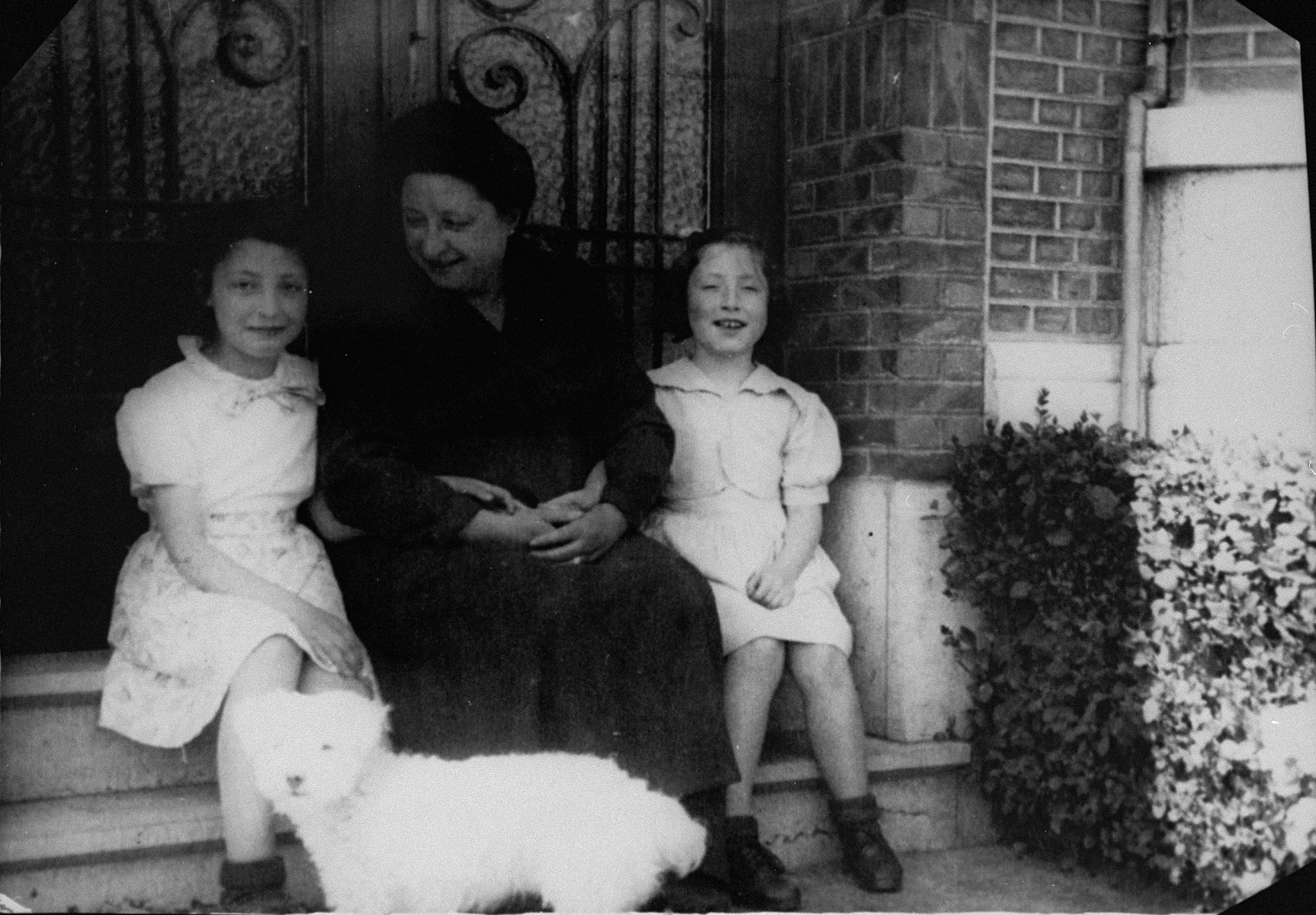 Margo and Annette Lederman, two Jewish children who lived in hiding with the van Buggenhout family during the war, pose with Clementine van Buggenhout, during a visit to her home after their removal to a Jewish orphanage.  Annette is the child who is crying.