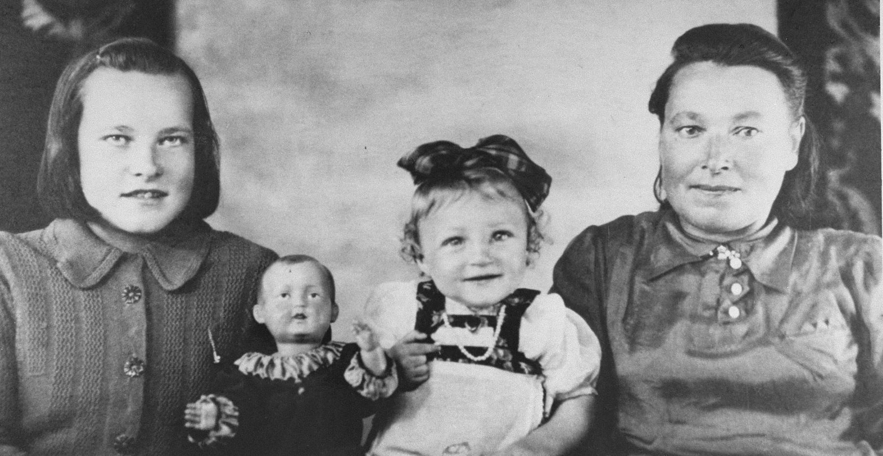 A Jewish child in hiding poses with members of the Lithuanian family that concealed her.  Pictured is the donor, Josephina Martul (right), and her daughter, Leonarda-Luisa (left)   Rose Levin (now Weinberg) is the daughter of Ida and Yossef Levin.  She was born in  March 1941 in Vilna.  Her older sister, Chaya, was born in 1936.  Her father was shot by the Germans shortly after the beginning of the German occupation.  Rose's mother then placed her with a Lithuanian family named Martul.  Rose passed as a relative whose name was Vera Martul.  After the death of her foster mother, Josephina Martul, Rose was cared for by the sixteen year-old daughter of the family, Lusia  Martul-Budrikiene.  Rose remained with Lusia Budrikene until 1957, when an aunt from Canada, Mrs. Friedman,  located her and arranged for her emigration to Toronto.  In 1993, Yad Vashem recognized Josephine Martul and her daughter Lusia Budrikiene as Righteous Among the Nations.