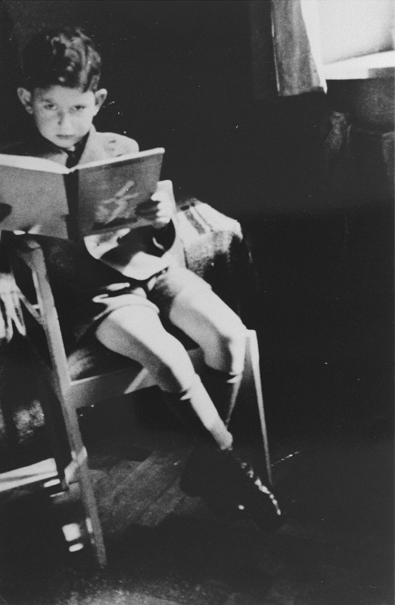 Jacob Gutgeld, a Jewish child from Warsaw, reads a book while living in hiding in the home of Alex and Mela Roslan.