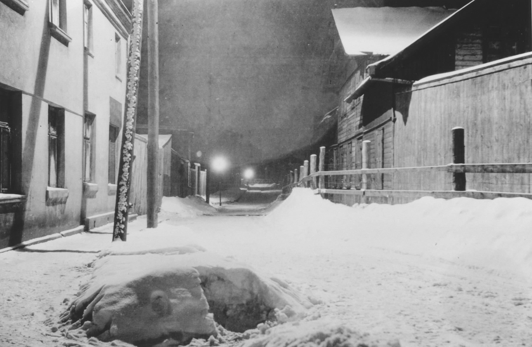 Night-time view of the fence and road enclosing the Lodz ghetto.  The photograph was probably taken by a member of Police Battalion 101.   One image from a photograph album belonging to a member of Police Battalion 101.