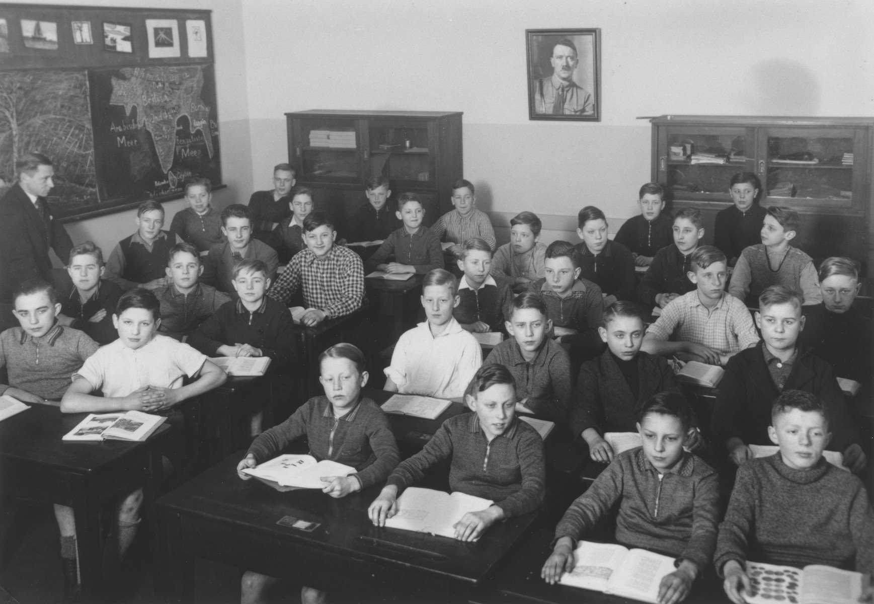German boys attend a geography lesson in a classroom adorned with a portrait of Adolf Hitler.   One image from a photograph album belonging to a member of Police Battalion 101.