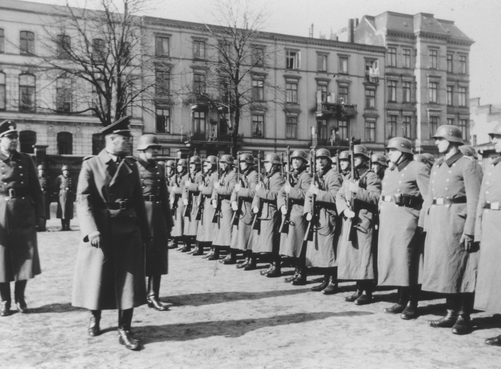 Inspection of members of Police Battalion 101 by their order police officers in a public square in Lodz.   One image from a photograph album belonging to a member of Police Battalion 101.