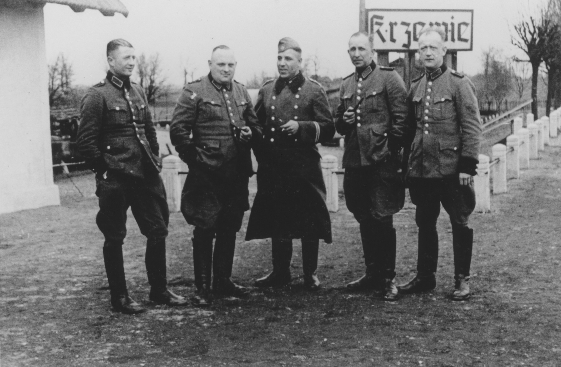 Group portrait of members of Police Battalion 101 beneath a sign that reads Krzewie.  One image from a photograph album belonging to a member of Police Battalion 101.